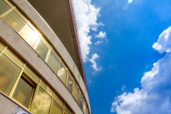 Perspective and underside angle view to textured background of modern glass building over blue sky.  stock image