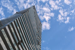 Perspective and underside angle view to textured background of modern glass building skyscrapers sunny day clouds sky Royalty Free Stock Image