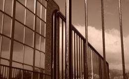 Perspective vertical lines angles fence building. Sepia toned image of iron railing with building in background Stock Photos