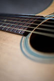 Acoustic guitar neck close-up. Perspective view of an acoustic guitar, looking at the sound hole and part of the neck Royalty Free Stock Photography