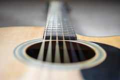 Acoustic guitar close-up. Perspective view of an acoustic guitar, looking from the sound hole up to the neck, which is out of focus Stock Image