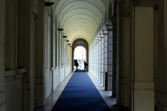 Perspective view of a colonnade gallery. With a blue carpet Royalty Free Stock Image