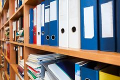 Perspective view at of colourful binders sorted on office shelves, archive Stock Image