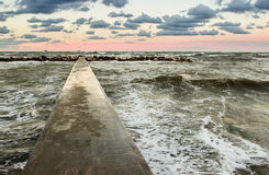 Perspective view of a concrete pier at the sea at sunset Royalty Free Stock Photos