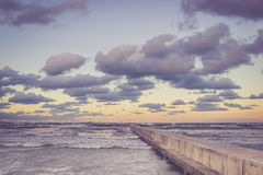 Perspective view of a concrete pier at the sea at sunset Stock Photo