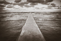 Perspective view of a concrete pier at the sea at sunset Stock Photography