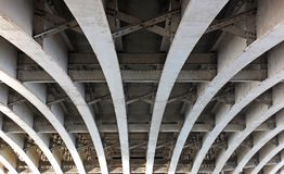 Perspective view of curved arch shaped steel girders under an old road bridge with rivets and struts painted grey royalty free stock photography