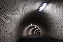 Perspective View Through a Dark Floodlighted Tunnel Royalty Free Stock Photography