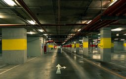 Perspective view of empty indoor car parking lot at the mall. Underground concrete parking garage with open lamp at night. White direction sign. Choose way to Stock Images