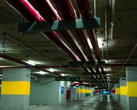 Perspective view of empty indoor car parking lot at the mall. Underground concrete parking garage with open lamp at night. Wiring. And plumbing in the mall Royalty Free Stock Image