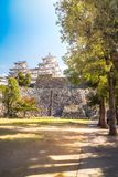Perspective View of Himeji Castle with large sunlit trees in Japan. Perspective View of Himeji Castle with large sunlit trees on the Castle complex park ground royalty free stock photography