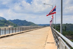 Perspective view of a long road dam, with Thai national flags. Stock Photo