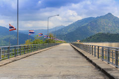 Perspective view of a long road dam, with Thai national flags along the road, mountain and clear blue sky background. Royalty Free Stock Images