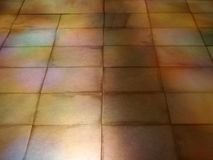 Perspective view of an old brown stone tiled floor with coloured light and sunlight reflections on the surface. A perspective view of an old brown stone tiled royalty free stock photos