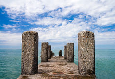 Perspective view of an old pier. With columns on Black Sea coast with perfect sky and sea on background. Russia, Sochi, Adler Royalty Free Stock Image
