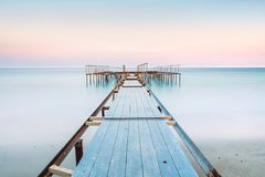 Long esposure view of a old jetty in a calm sea with gentle sky,. Perspective view of a old pier in a completely calm sea with gentle sky and clouds. Long Royalty Free Stock Photos