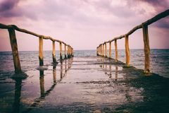 Perspective view of a pier on the seashore with clear blue sea and dramatic sky Royalty Free Stock Photos