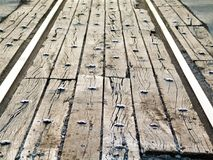 Perspective view of rail road tracks street crossing with old wood and bolts - selective focus Royalty Free Stock Images
