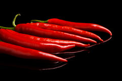 Perspective view of red peppers isolated black background. Perspective view of chilli red peppers isolated on black background Royalty Free Stock Image