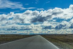 Perspective view of road trip on asphalt road in sunlight with beautiful nature golden yellow grass in autumn in cloudy blue sky. Through national park south stock images