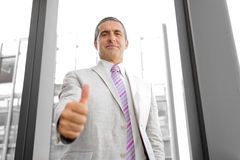 Perspective view of a smiling businessman with thumb up Stock Photography