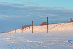 Perspective view of snowy poles in the sunset time Stock Photos