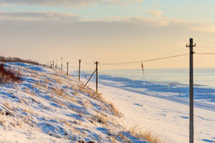 Perspective view of snowy poles in the sunset time Royalty Free Stock Images