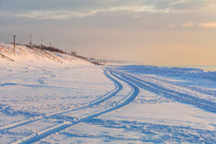 Perspective view of snowy poles in the sunset time Stock Photography
