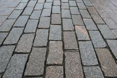 Perspective view on stone road close up. Pavement of granite. Brown square cobblestone sidewalk. Mock up or vintage stock photography