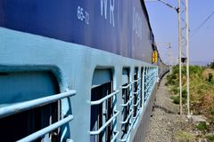 Journey in indian railways train. Rail passengers transportation in India. Perspective view to indian railways blue train with windows with gates. India rail stock photos