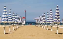 Closed Umbrellas - Rimini Beach, Italy. Perspective view of two rows of closed umbrellas at the beginning of the season in Rimini, the most famous seaside place Royalty Free Stock Image
