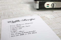 Perspective view from a waffle recipe with a waffle iron in the background Stock Images