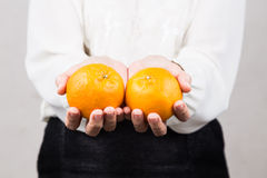 Perspective view woman giving mandarin oranges during Chinese Ne Stock Image