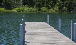 Perspective view of wood and metal dock on a lake. Metal and wood boat dock projectiong into a lake with woodland shoreline backdrop Stock Photos