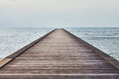 Perspective view of a wooden pier in tropical sea Royalty Free Stock Photos