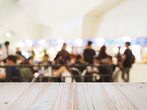 Perspective wood and blurred food court with crowd people. Stock Photo