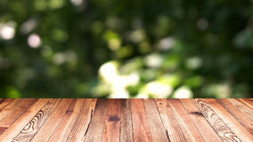 Perspective wood and bokeh light background. product display template. Wood table top on blur moving natural green leaf. Background Royalty Free Stock Images