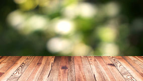 Perspective wood and bokeh light background. product display template. Wood table top on blur moving natural green leaf. Background Stock Photo