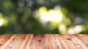 Perspective wood and bokeh light background. product display template. Wood table top on blur moving natural green leaf. Background Stock Images