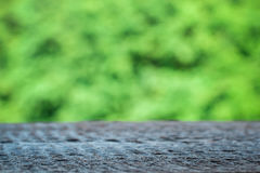 Wooden table on a background of bright green trees in the defocus. Perspective wood over blur trees with bokeh background, spring and summer season Royalty Free Stock Photo