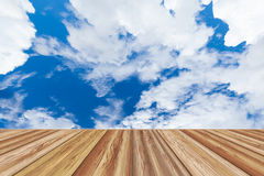 Perspective wooden board empty table top over beautiful blue sky. With cloudy at the daytime on summer day. Can be used for montage or display your products Royalty Free Stock Images