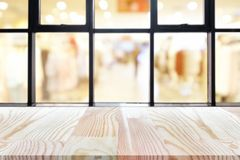 Perspective wooden board empty table on top over blurred coffee shop background, can be used mock up for display of product or royalty free stock images