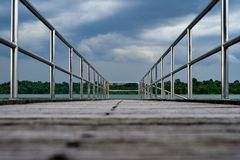 Wooden bridge perspective storm cloud. Perspective of a wooden bridge in low angle, stainless steel railing and stormy clouds Stock Photography