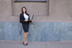 Perspective young girl asian entrepreneur holds laptop and works Stock Photography