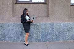 Perspective young girl asian entrepreneur holds laptop and works Stock Images