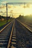 Perspektiv av järnvägar i det gula ljuset för afton Arkivfoton