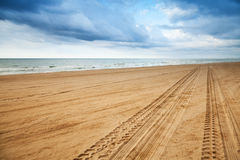 Perspektive von Reifenbahnen auf sandigem Strand Stockfoto