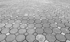 Perspektiven-Ansicht des monotonen Schmutzes Gray Brick Stone aus den Grund für Straßen-Straße Bürgersteig, Fahrstraße, Straßenbe stockfotos
