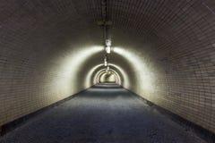 Perspektiven-Ansicht durch einen dunklen Floodlighted Tunnel Stockfotos