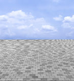 Perspektiven-Ansicht von monotonem Gray Brick Stone Street Road Bürgersteig, Pflasterungs-Beschaffenheits-Hintergrund mit blauem  Lizenzfreie Stockfotografie